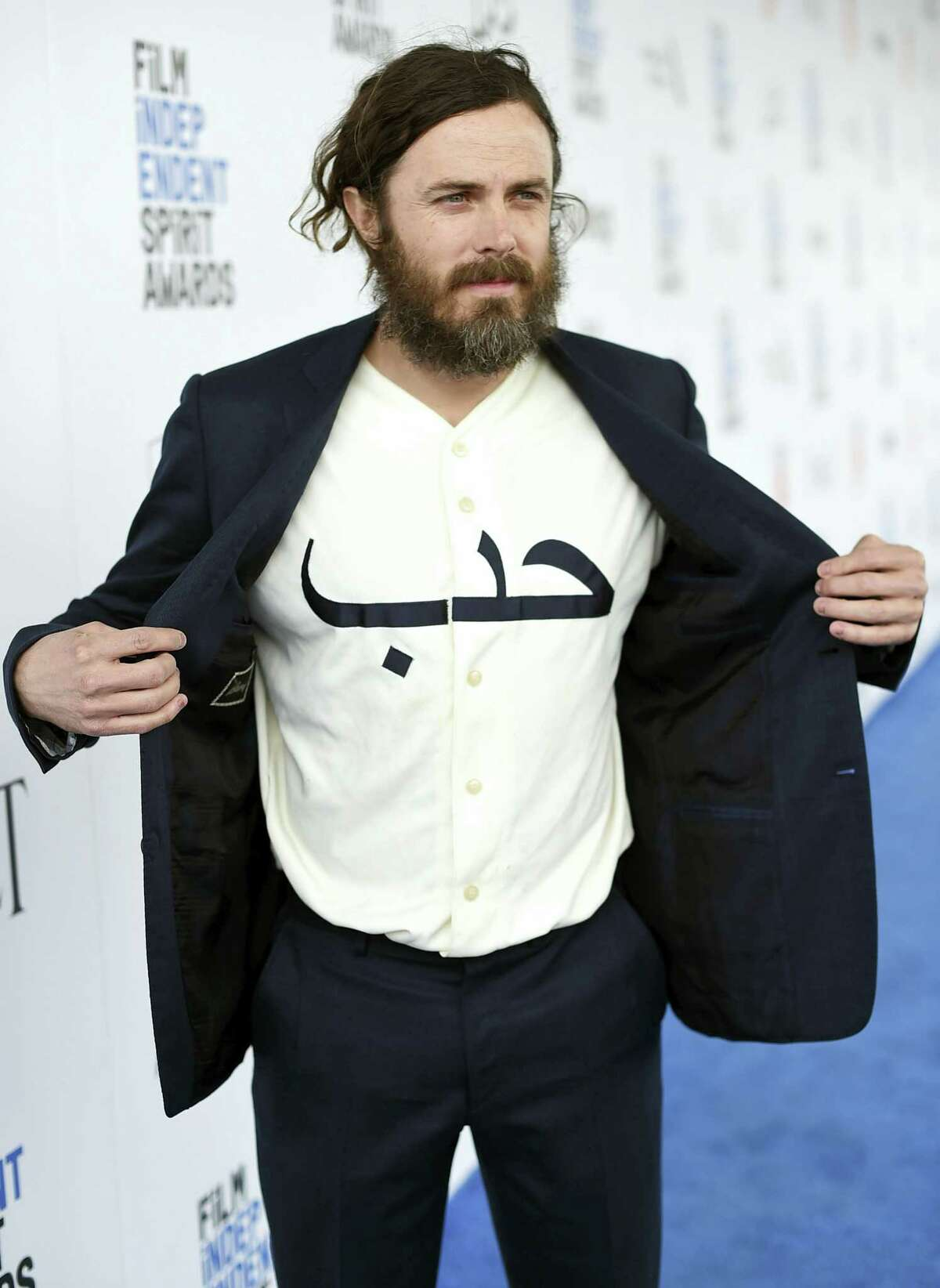 """Casey Affleck displays his shirt with the Arabic word """"love"""" as he arrives at the Film Independent Spirit Awards on Feb. 25, 2017 in Santa Monica, Calif."""