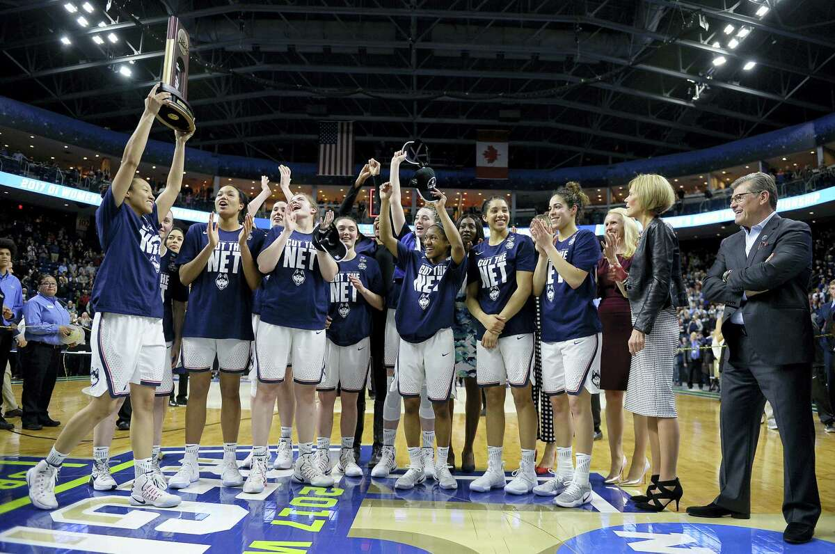 UConn's Saniya Chong holds the trophy as her teammates cheer following their 90-52 win over Oregon in the NCAA Tournament regional final in Bridgeport on Monday.