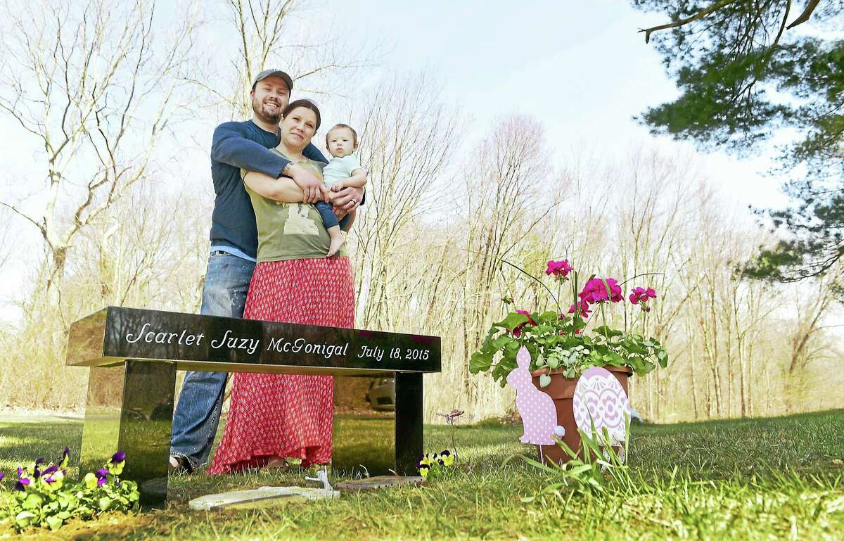 Jim and Katie McGonigal of Woodbridge with their daughter Althea, 9 months, at the grave of their stillborn baby, Scarlet Suzy McGonigal, at the East Side Cemetery in Woodbridge.