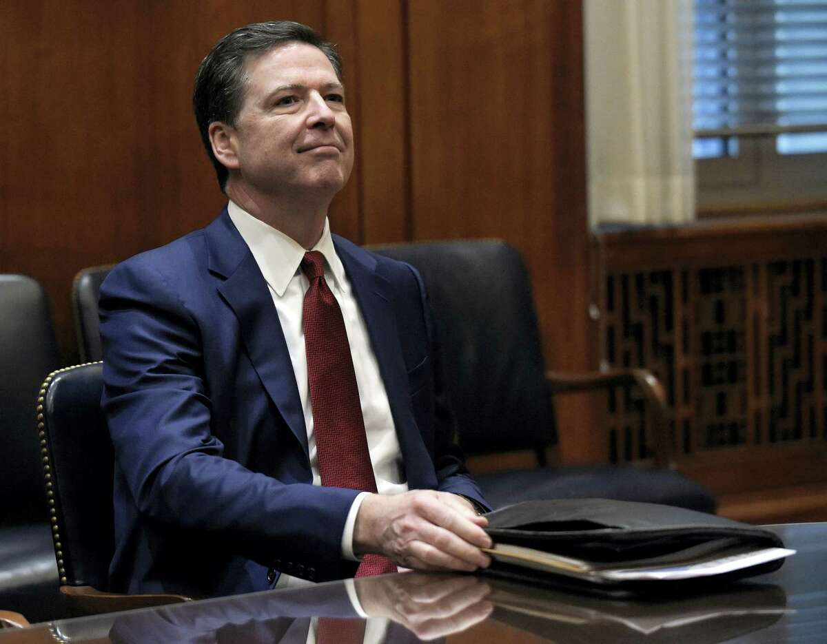In this Feb. 9, 2017, file photo, FBI Director James Comey waits for the start of a meeting with Attorney General Jeff Session and the heads of federal law enforcement components at the Department of Justice in Washington. Comey is again in a familiar spot these days _ the middle of political tumult. As a high-ranking Justice Department official in the George W. Bush administration, he clashed with the White House over a secret surveillance program. Years later as head of the FBI, he incurred the ire of Hillary Clinton supporters for public statements on an investigation into her emails. Now, Comey is facing new political pressure as White House officials are encouraging him to follow their lead by publicly recounting private FBI conversations in an attempt to dispute reports about connections between the Trump administration and Russia.