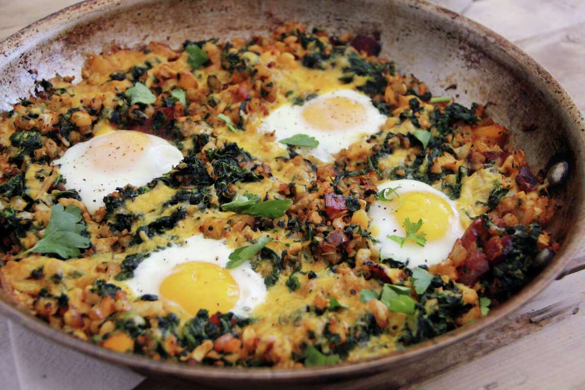 A country-style breakfast skillet with eggs, bacon and vegetables.