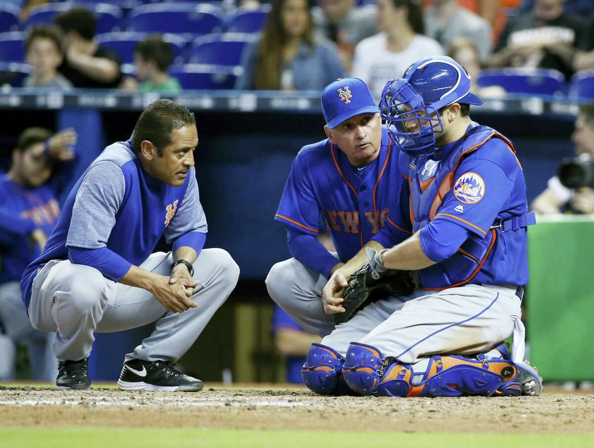 New York Mets manager Terry Collins, center, and a trainer attend to catcher Travis d'Arnaud after a play during the ninth inning Sunday.