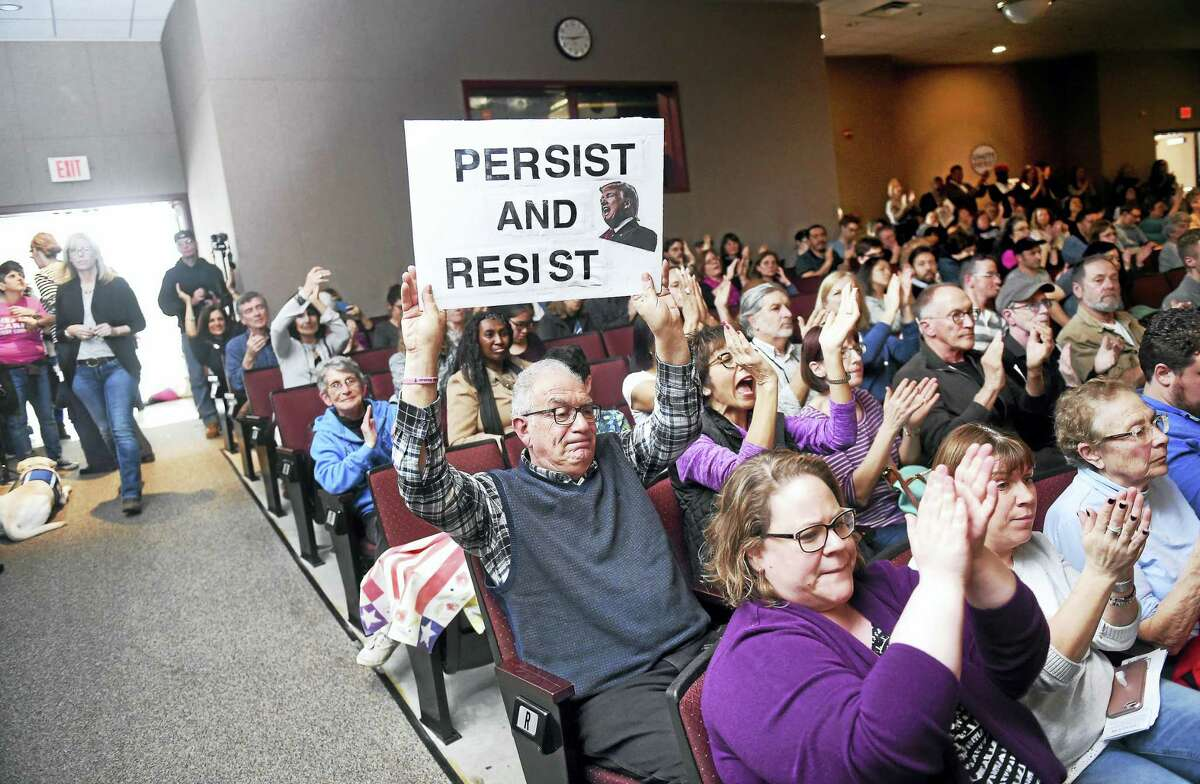 Peter Bunzl (center) of Oxford displays a sign opposing President Donald Trump during a Town Hall meeting with U.S. Senator Richard Blumenthal at Wilbur Cross High School in New Haven on Feb. 25, 2017.