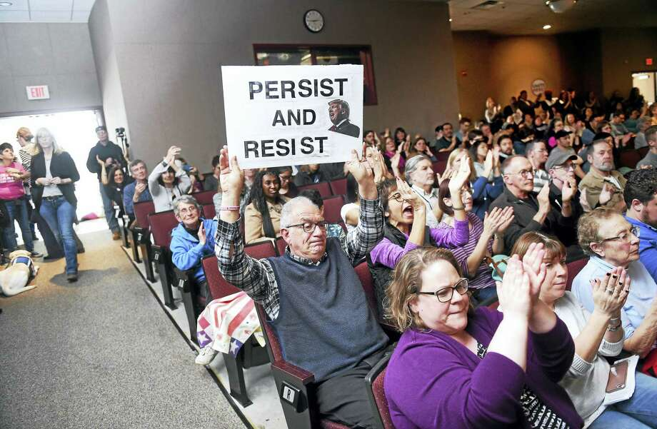 Peter Bunzl (center) of Oxford displays a sign opposing President Donald Trump during a Town Hall meeting with U.S. Senator Richard Blumenthal at Wilbur Cross High School in New Haven on Feb. 25, 2017. Photo: Arnold Gold-New Haven Register