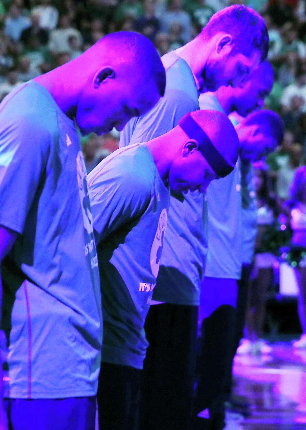 The Celtics' Isaiah Thomas and teammates bow their heads during a moment of silence for Thomas' sister Chyna before Sunday's game.