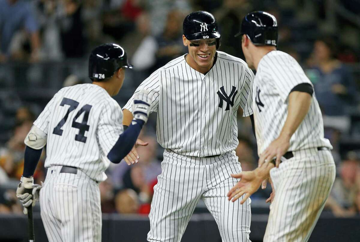 The Yankees' Ronald Torreyes (74) congratulates Aaron Judge and Chase Headley (12) who both scored on a double by Austin Romine in the eighth inning Sunday at Yankee Stadium in New York.