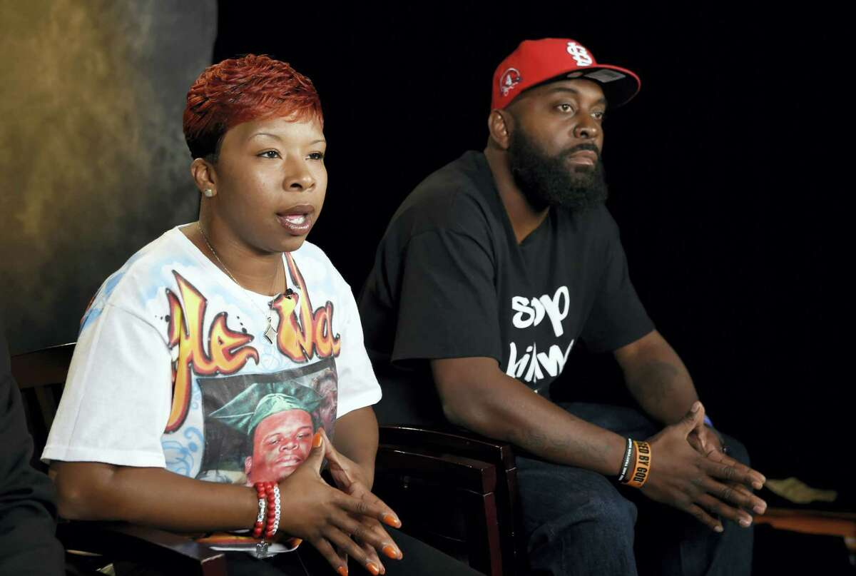 In this Sept. 27, 2014, file photo, the parents of Michael Brown, Lezley McSpadden, left, and Michael Brown Sr., sit for an interview with The Associated Press in Washington. The city attorney in Ferguson, Missouri, said Friday, June 23, 2017, that the city's insurance company paid $1.5 million to settle a lawsuit filed by the family of Michael Brown.