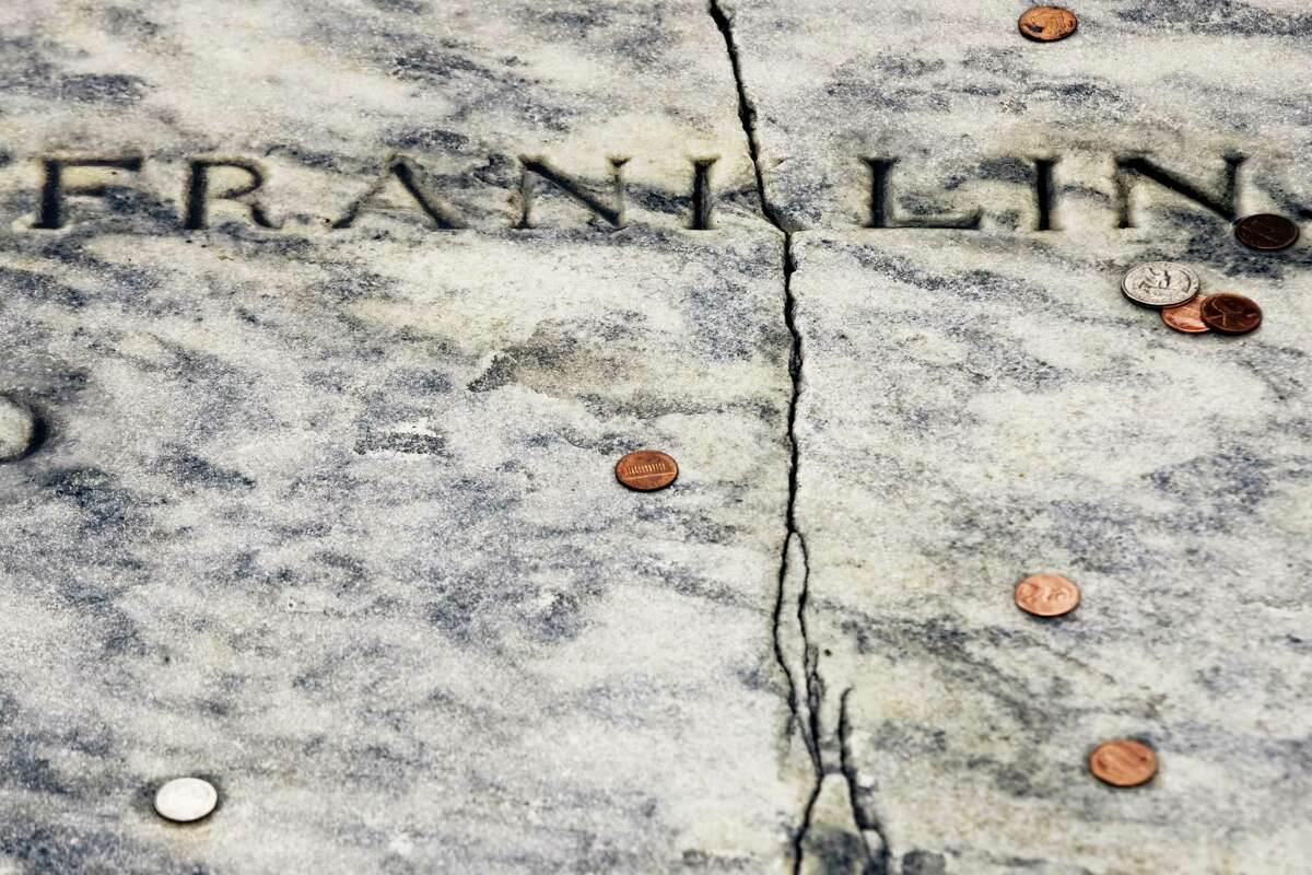 In this Tuesday, Nov. 15, 2016, file photo, a crack runs through Benjamin Franklin's a gravestone at the Christ Church Burial Ground in Philadelphia. Repairs are complete on Franklin's damaged gravestone. KYW-TV reported Christ Church will hold an unveiling Tuesday, May 23, 2017, of the repaired slab on the grave that holds Franklin and his wife, Deborah.