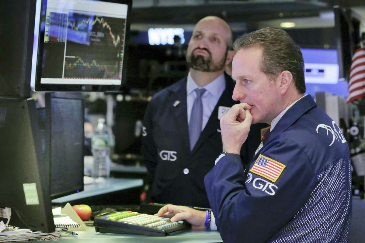 Specialists Glenn Carell, right, and James Denaro work on the floor of the New York Stock Exchange Monday.