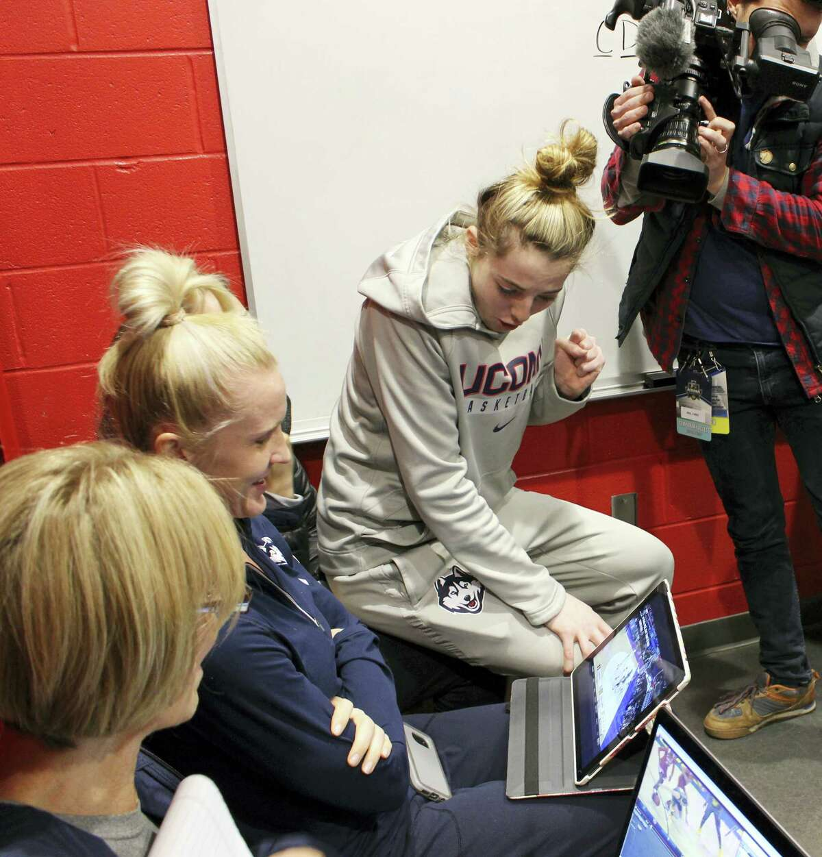 UConn's Katie Lou Samuelson watches a computer in the team's locker room in Bridgeport as her sister Karlie's Stanford team takes on Notre Dame in the Lexington regional on Sunday.