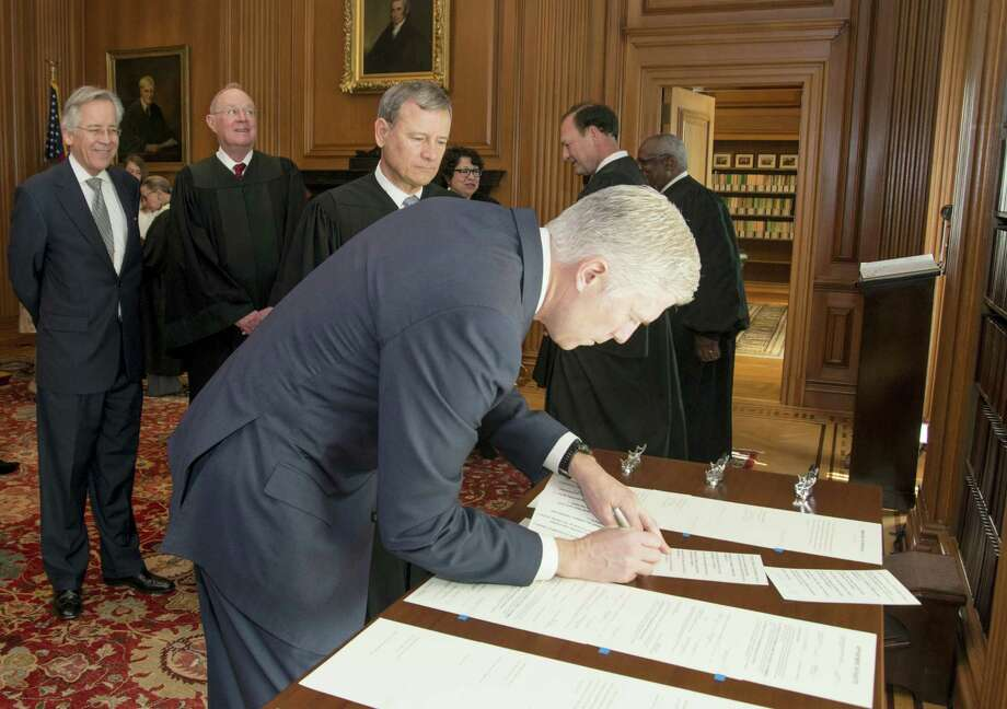 In this photo provided by the Public Information Office Supreme Court of the U.S., Chief Justice John Roberts, Jr., and fellow justices watch as Neil Gorsuch signs the Constitutional Oath after Roberts administered the Constitutional Oath in a private ceremony recently. Photo: Franz Jantzen — Public Information Office Supreme Court Of The U.S. Via AP   / Franz Jantzen, Collection of the Supreme Court of the United States