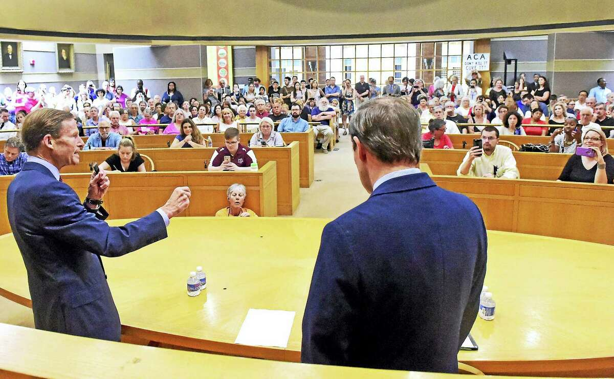 U.S. Sens. Richard Blumenthal, left, and Chris Murphy, right, speak to a crowd at New Haven City Hall Friday to receive public testimony on the Senate health care overhaul.