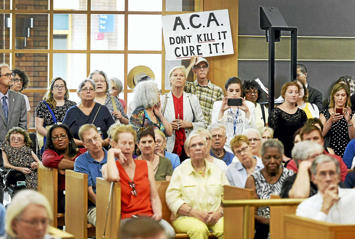 Hap Jordan of Cheshire, holding sign, and others attend Friday's health care reform discussion in New Haven.