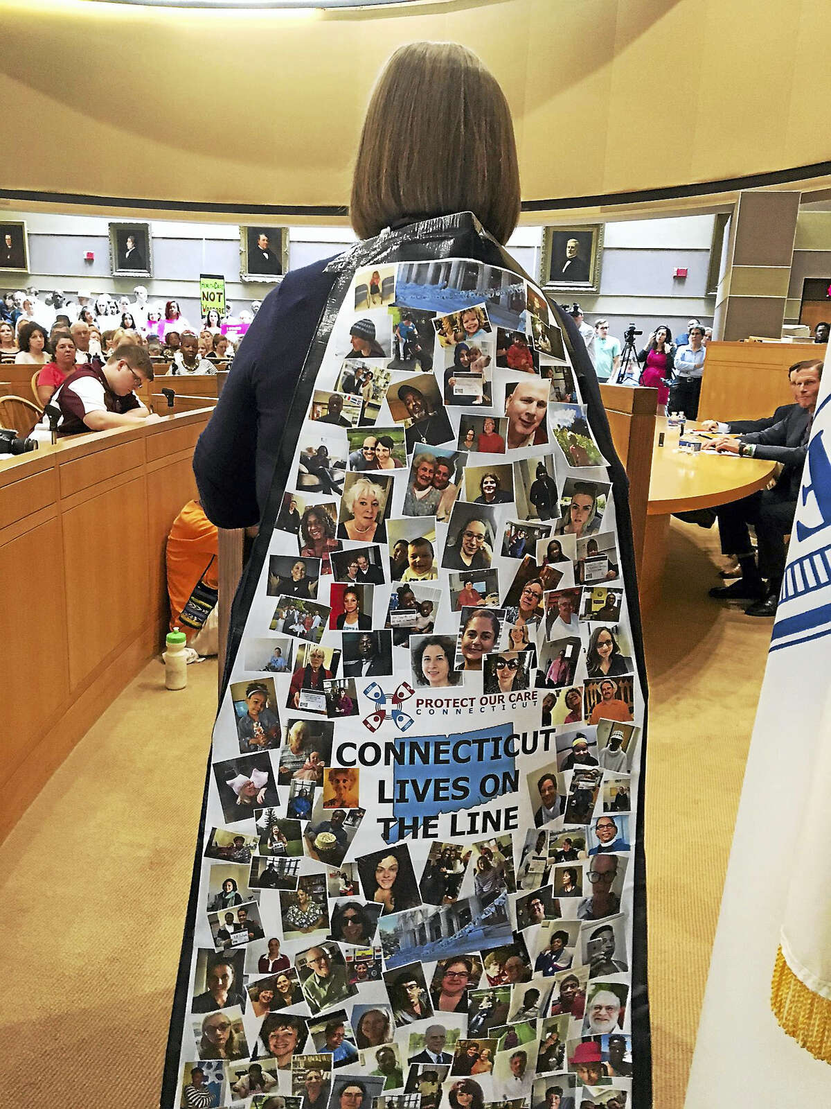 Lynn Ide of the Health Care Foundation of Connecticut wears a cape that has photos of people who say their lives are threatened if health care is cut.