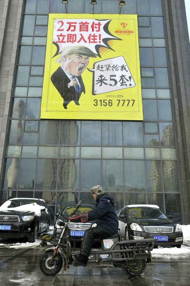A motorcyclist drives past a real estate advertisement featuring a cartoon figure resembling U.S. President Donald Trump in Shenyang in northeastern China's Liaoning province Wednesday, Feb. 22, 2017. After years of legal wrangling, China's government awarded Trump's business valuable rights to his own name last week, in the form of a 10-year trademark for construction services. Photo: Chinatopix Via AP    / Chinatopix