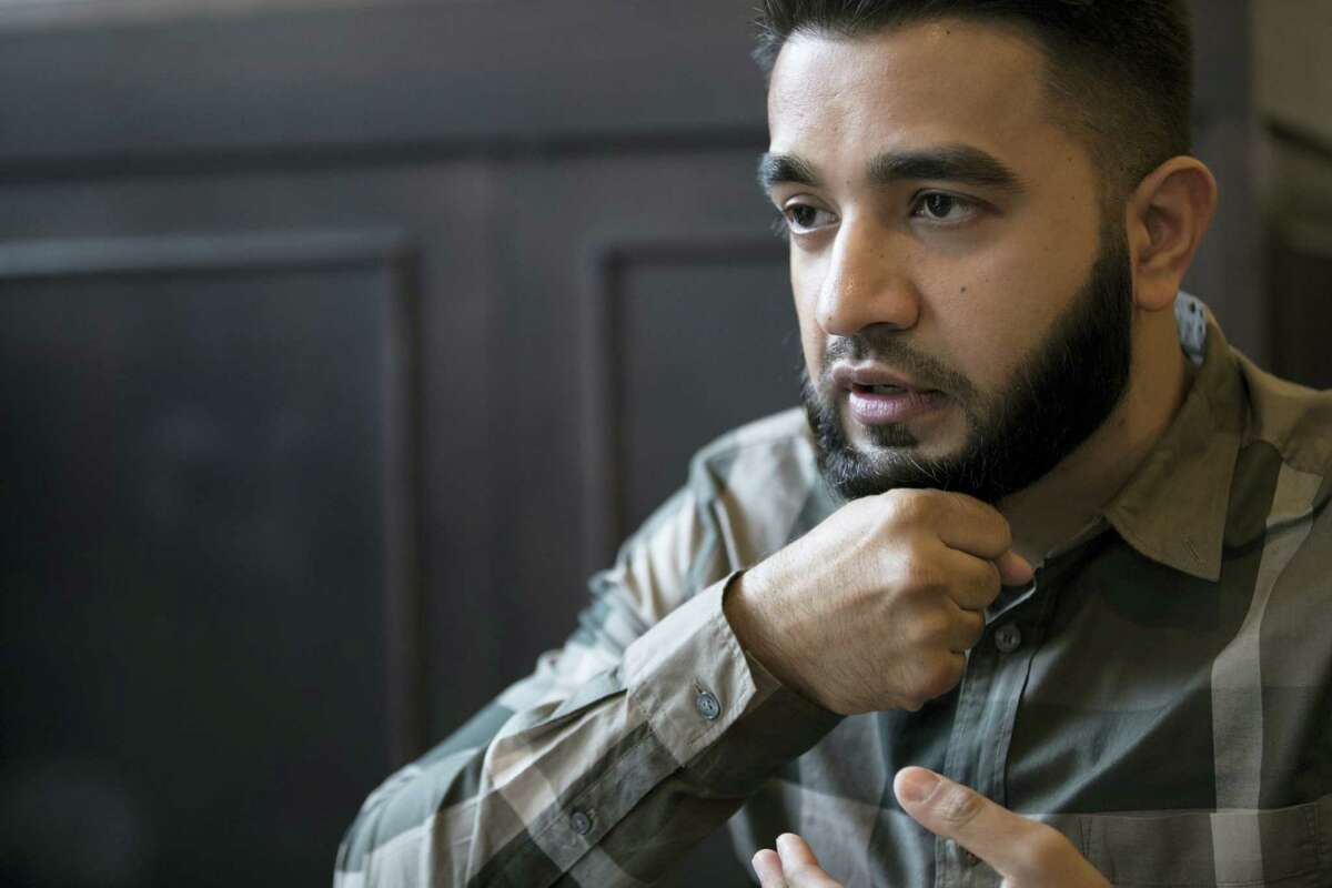 New York City police officer Masood Syed demonstrates a fistful, the required length of a beard for Muslim men, during an interview with The Associated Press in New York. Police departments around the country, compelled by a hiring crisis and eager for a more diverse applicant pool, are relaxing traditional grooming standards. That means more officers are on the job with tattoos inked on forearms and biceps, wearing religious headgear like hijabs and turbans, and growing out beards.