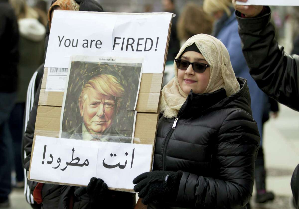 A woman carries a sign outside of the White House during a demonstration to denounce President Donald Trump's executive order that bars citizens of seven predominantly Muslim-majority countries from entering the United States on Sunday in Washington.