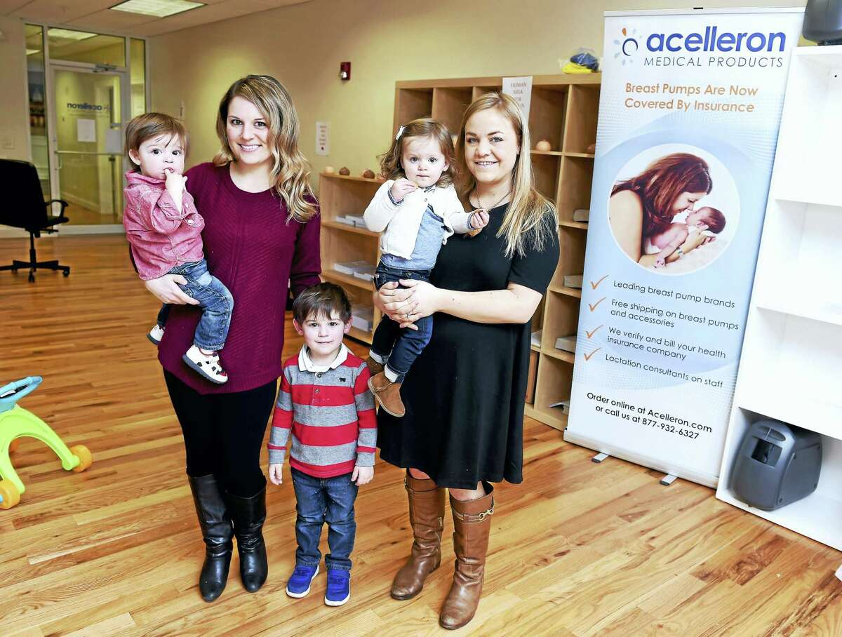 Left to right, Jacqui Penda of Branford with her sons, Luke, 1, and Dylan, 3, and Faye Klein of Fairfield with her daugher, Reese, 2, are photographed at Acelleron Medical Products in Guilford. Penda is a donor to Mothers' Milk Bank Northeast and Klein's daughter is a recipient of donated milk.
