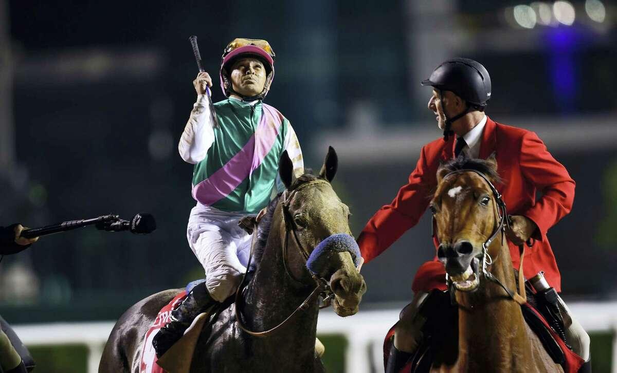 Mike Smith, atop Arrogate, celebrates after winning the $10 million Dubai World Cup at the Meydan Racecourse in Dubai, United Arab Emirates on Saturday.