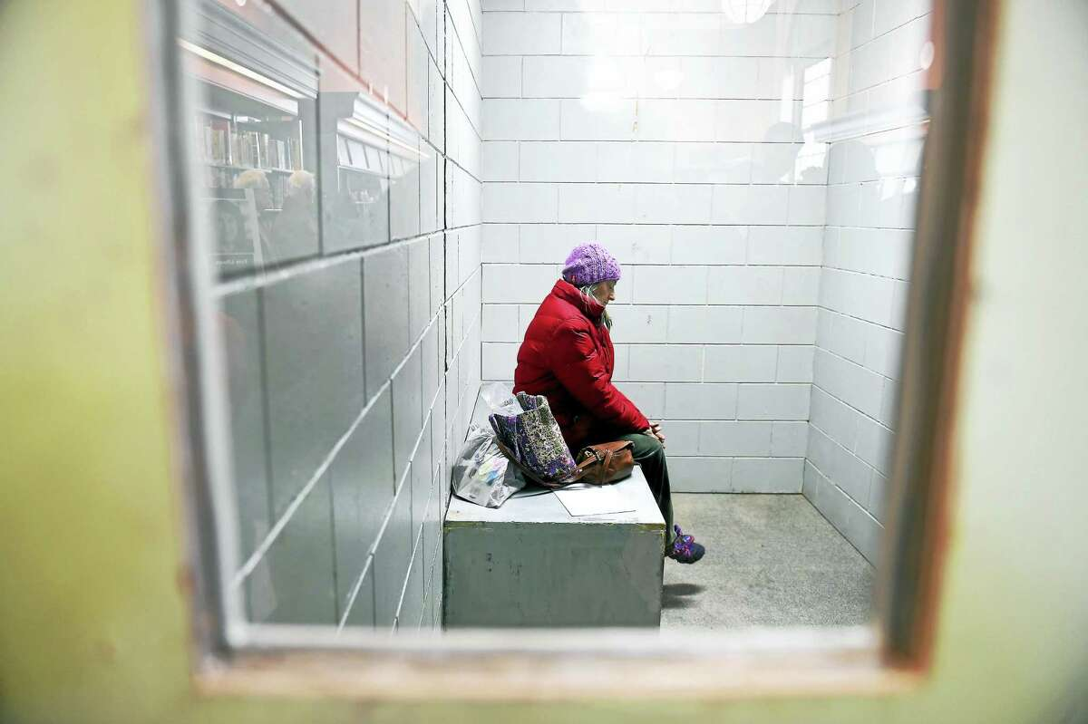 Anne Burns of New Haven sits inside a replica solitary confinement cell set up inside the New Haven Free Public Library Monday.