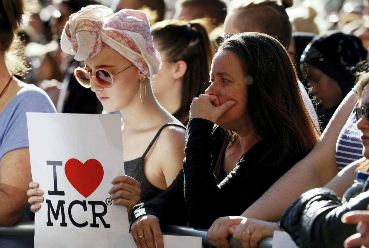 People attend a vigil in Albert Square, Manchester, England, Tuesday May 23, 2017, the day after the suicide attack at an Ariana Grande concert that left 22 people dead as it ended on Monday night.