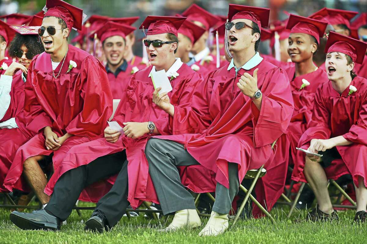 From left, Luis Galindo, Scott Bohannon and Santino Barnabei cheer for their classmates receiving their diplomas at Wilbur Cross High School graduation Thursday.