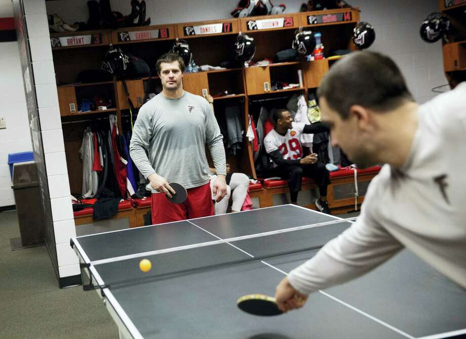 The Falcons' Andy Levitre, left, plays against teammate Josh Harris in a game of pingpong in the locker room at the team's practice facility in Flowery Branch, Ga. For the Super Bowl-bound Falcons, brotherhood begins at three pingpong tables in the middle of their locker room. That's where friendships are forged, friendly wagers settled and the competitive juices really get flowing. Photo: David Goldman — The Associated Press   / Copyright 2017 The Associated Press. All rights reserved.