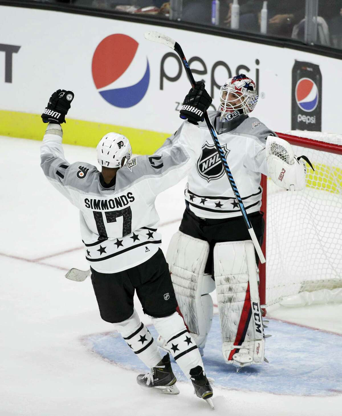 Metropolitan Division's Wayne Simmonds, left, of the Philadelphia Flyers, and goalie Braden Holtby, of the Washington Capitals, celebrate their team's win in the NHL All-Star Game on Sunday in Los Angeles.