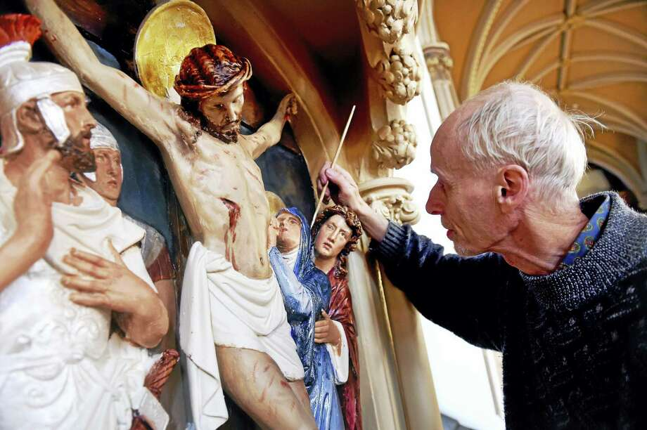 Henry Pospieszalski paints the 12th Station of the Cross at the Church of the Assumption in Ansonia recently. Photo: Arnold Gold — New Haven Register