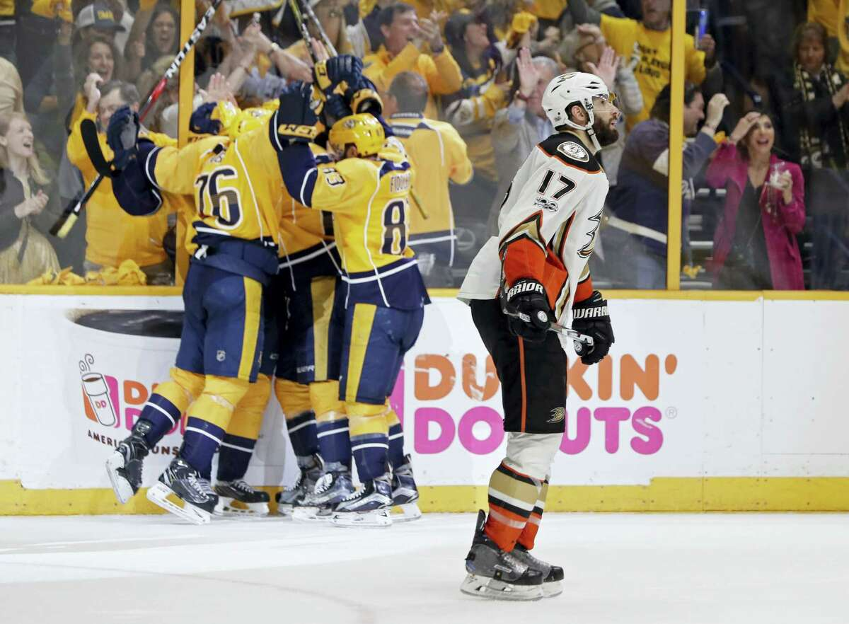 Ducks center Ryan Kesler (17) skates past as Predators players celebrate an empty-net goal during the third period on Monday.