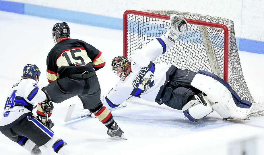 New Haven Police goalie Justin Eddy (right) dives to black a shot from Mike Pomichter (left) of the New Haven Fire Department during the 2017 Chief's Cup at Ingalls Rink in New Haven on March 25, 2017. Photo: Arnold Gold-New Haven Register