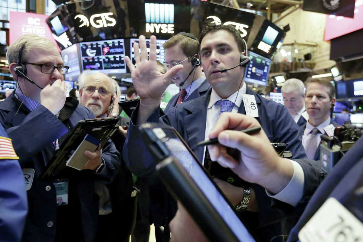 Trader Craig Spector, center, works in a crowd on the floor of the New York Stock Exchange Thursday.