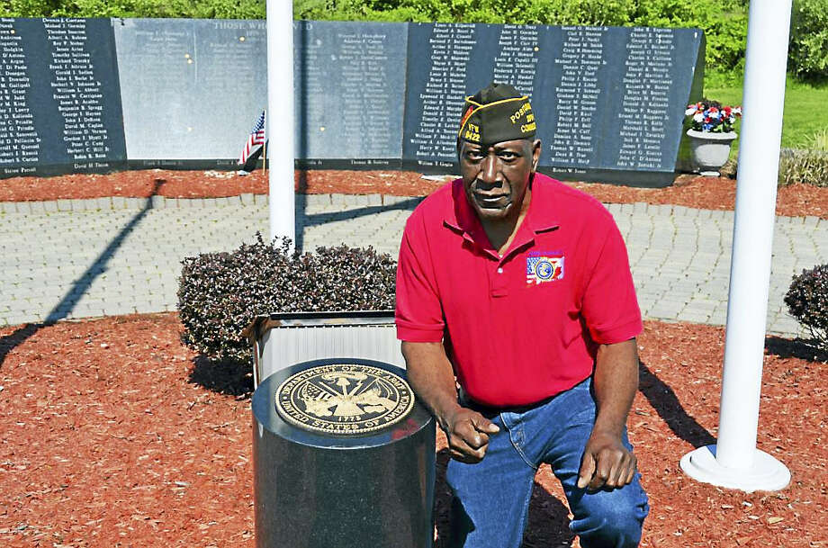 Veterans of Foreign Wars Post 9422 Cmdr. Freddy Jackson kneels beside the granite U.S. Army insignia marker May 11, 2016, at the Vietnam Veterans Memorial in Bradley Point Park. Photo: Contributed Photo — Michael P. Walsh, City Of West Haven