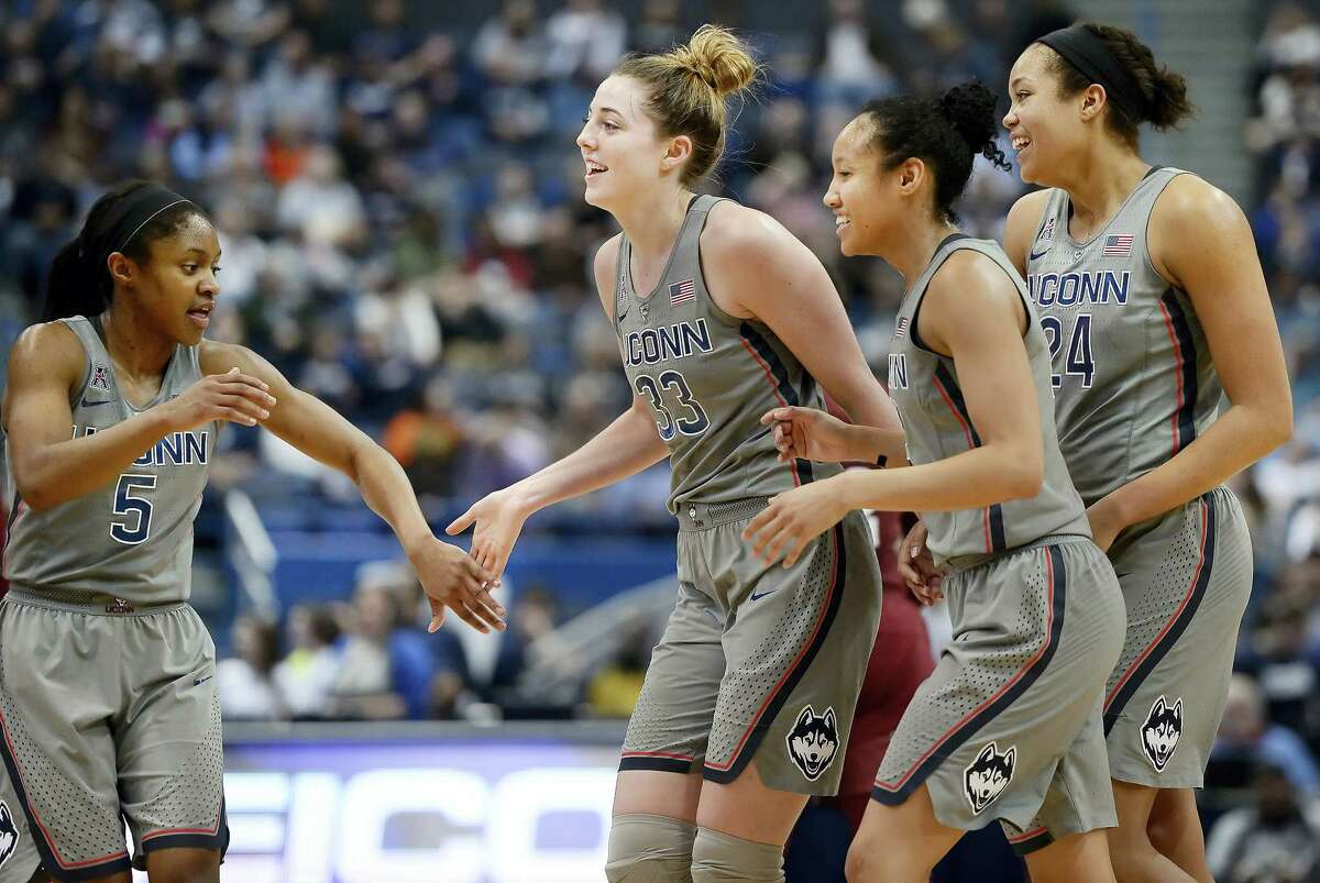 Connecticut's Crystal Dangerfield, Katie Lou Samuelson, Saniya Chong and Napheesa Collier, from left, celebrate as they come off the court for a timeout in the second half of an NCAA college basketball game against Temple, Wednesday in Hartford, Conn.