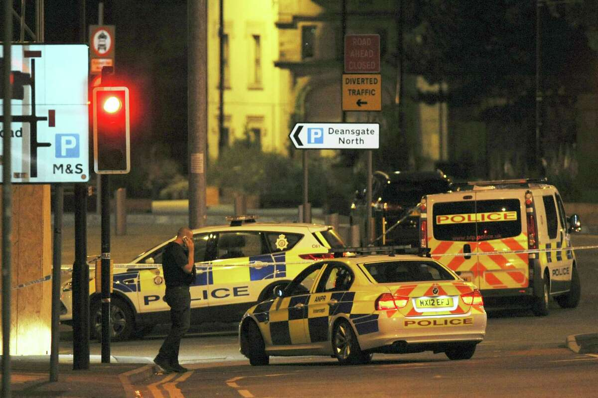 Armed police block a road near to the Manchester Arena in central Manchester, England, Tuesday. An explosion struck an Ariana Grande concert in northern England late Monday, killing over a dozen people and injuring dozens in what police say they are treating as a terrorist attack.
