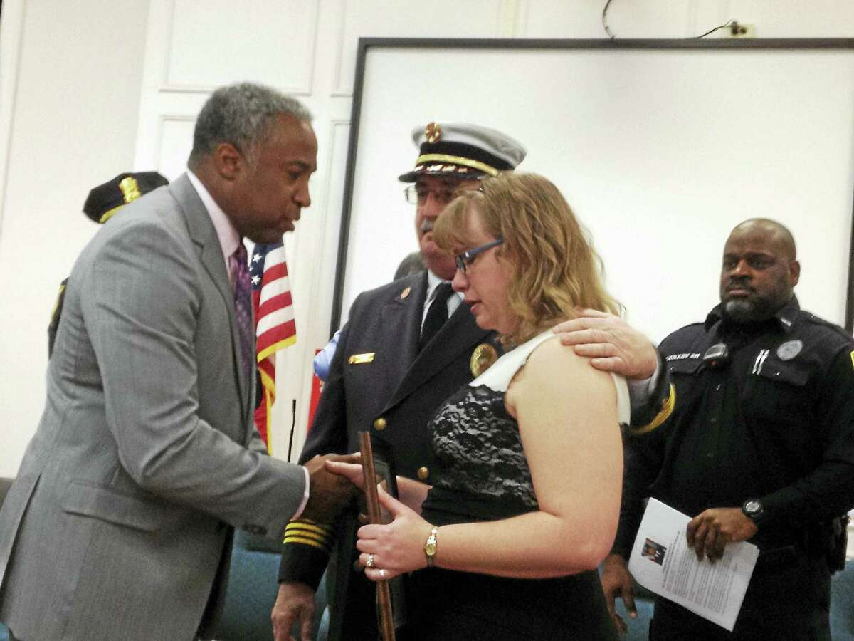 John Lewis, left, executive assistant to Mayor Ed O'Brien, presents a citation Wednesday to Christina Smith, center, whose late husband, West Haven Fire Department firefighter Ransford Smith Jr., was honored as African-American Citizen of the Year along with police officer Marcus Tavares, far right. West Haven Fire Department Chief Jim O'Brien comforts Smith at the 21st Annual West Haven Black Heritage Celebration in City Hall.