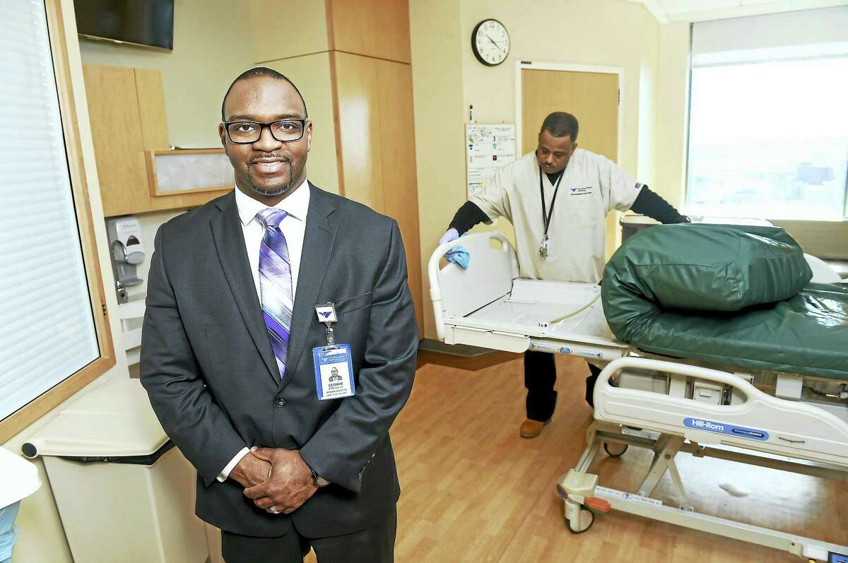 George Pressley, left, System Director for ABM Healthcare Support Services, is photographed in a room in the Smilow Cancer Hospital with Anthony Harris cleaning a bed.