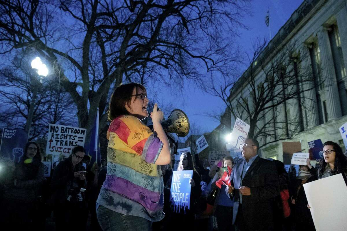 Activists and protesters with the National Center for Transgender Equality rally in front of the White House, Wednesday in Washington, after the Department of Education and the Justice Department announce plans to overturn the school guidance on protecting transgender students.