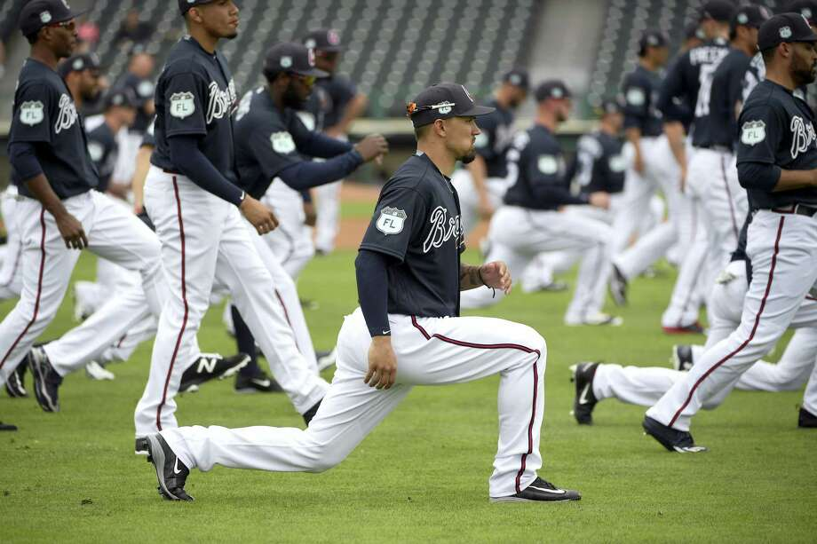 Atlanta Braves infielder Jace Peterson, center, stretches with teammates during the first full-squad spring training workout in Lake Buena Vista, Fla. on Feb. 18, 2017. Photo: AP Photo/Phelan M. Ebenhack   / FR121174 AP