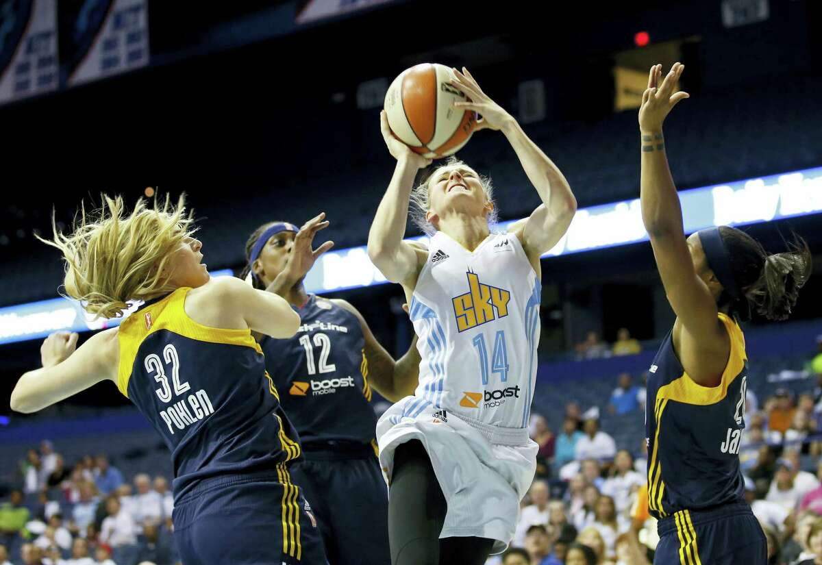 Chicago Sky guard Allie Quigley (14) goes to the basket against the defense of Indiana Fever's guard Jeanette Pohlen (32), center Lynetta Kizer (12) and guard Briann January, right, during the first half of Game 3 of the WNBA basketball Eastern Conference semifinals on Sept. 21, 2015 in Rosemont, Ill.