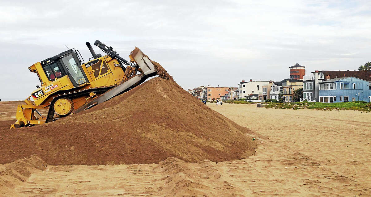 In this 2015 file photo, a bulldozer piles sand into a high berm to protect homes along Sunset Beach in Huntington Beach, Calif. The state's Ocean Protection Council decided weeks ago to update its sea-rise guidance for state and local governments.