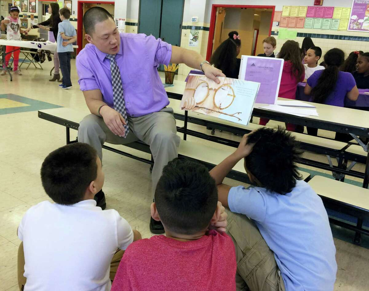 In this Feb. 14, 2017 photo, teacher Craig Muzzy reads a story about peer pressure to students at the Chamberlain Elementary School in New Britain, Conn., as part of the Love Wins program's Friendship Day. The emotional-learning program is designed to deal with the problem of social isolation and teach students about empathy.