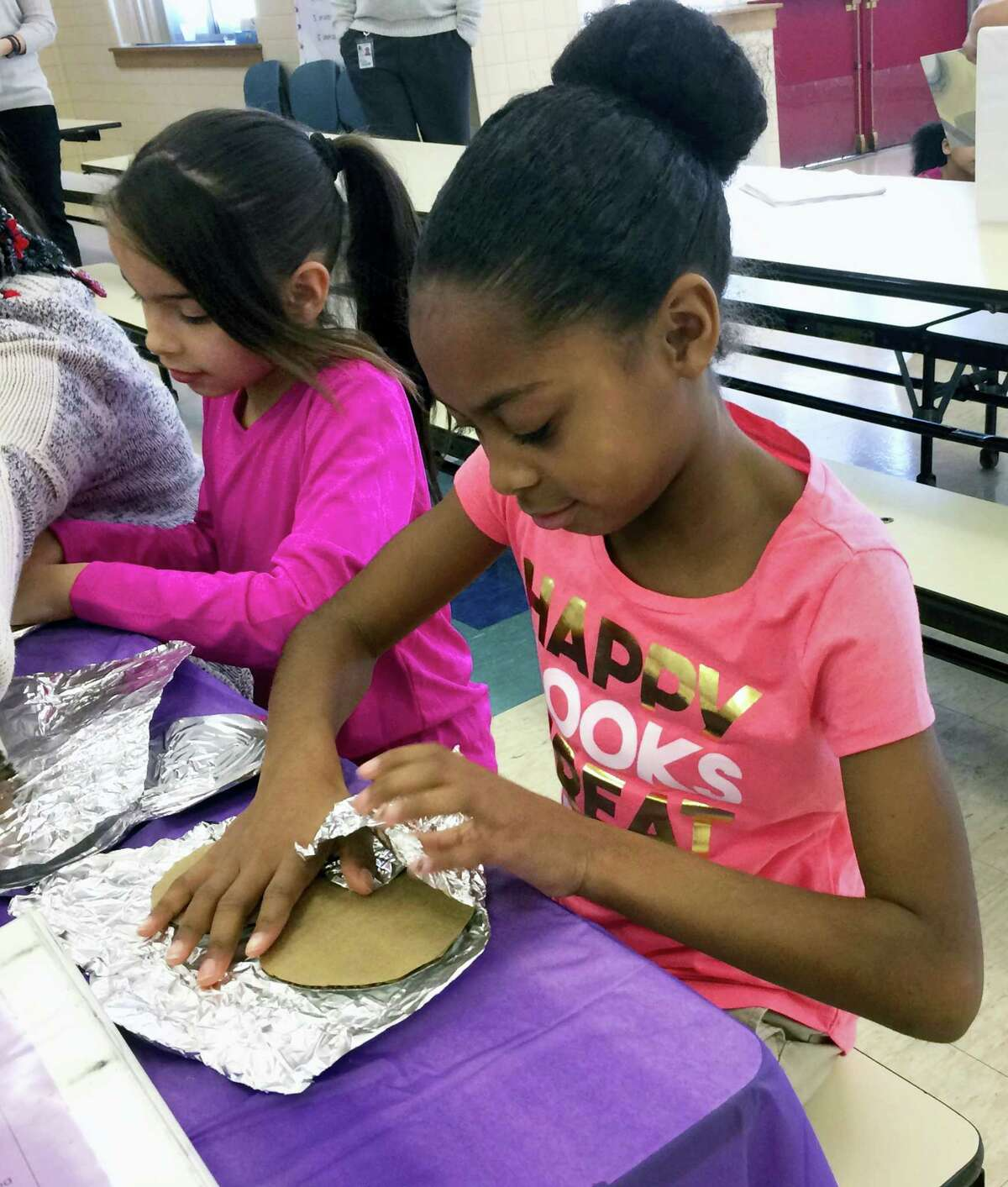 In this Feb. 14, 2017 photo, fourth-graders Jazyre Guzman, left, and Zariah Thomas, right, create tin foil hearts as part of the Love Wins Friendship Day at Chamberlain Elementary school in New Britain, Conn. The program is designed to deal with the problem of social isolation and teach students about empathy. (AP Photo/Pat Eaton-Robb)