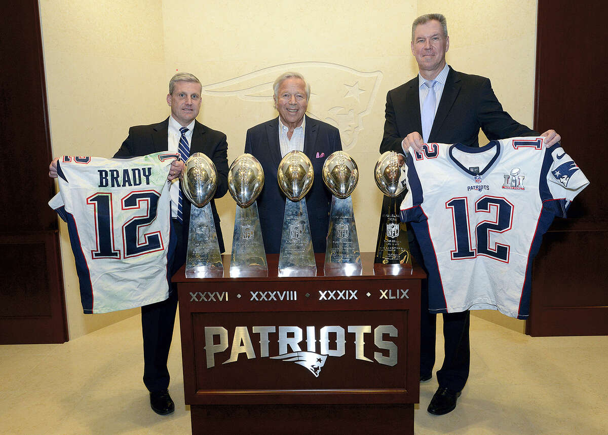 In this photo released by the Federal Bureau of Investigation, Harold H. Shaw, left, Special Agent in Charge of the FBI Boston Division and Colonel Richard D. McKeon, right, of the Massachusetts State Police, hold two recovered Super Bowl jerseys worn by New England Patriots quarterback Tom Brady, beside team owner Robert Kraft, center, on Thursday in the team's trophy room at Gillette Stadium.