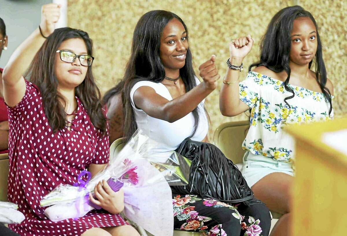 From left, graduates Sheena Carreto, Ahjolee K. Bolden and Demani Brown respond to keynote speaker Don Sawyer III, assistant professor of sociology at Quinnipiac University, during the New Light High School celebration Tuesday in New Haven.