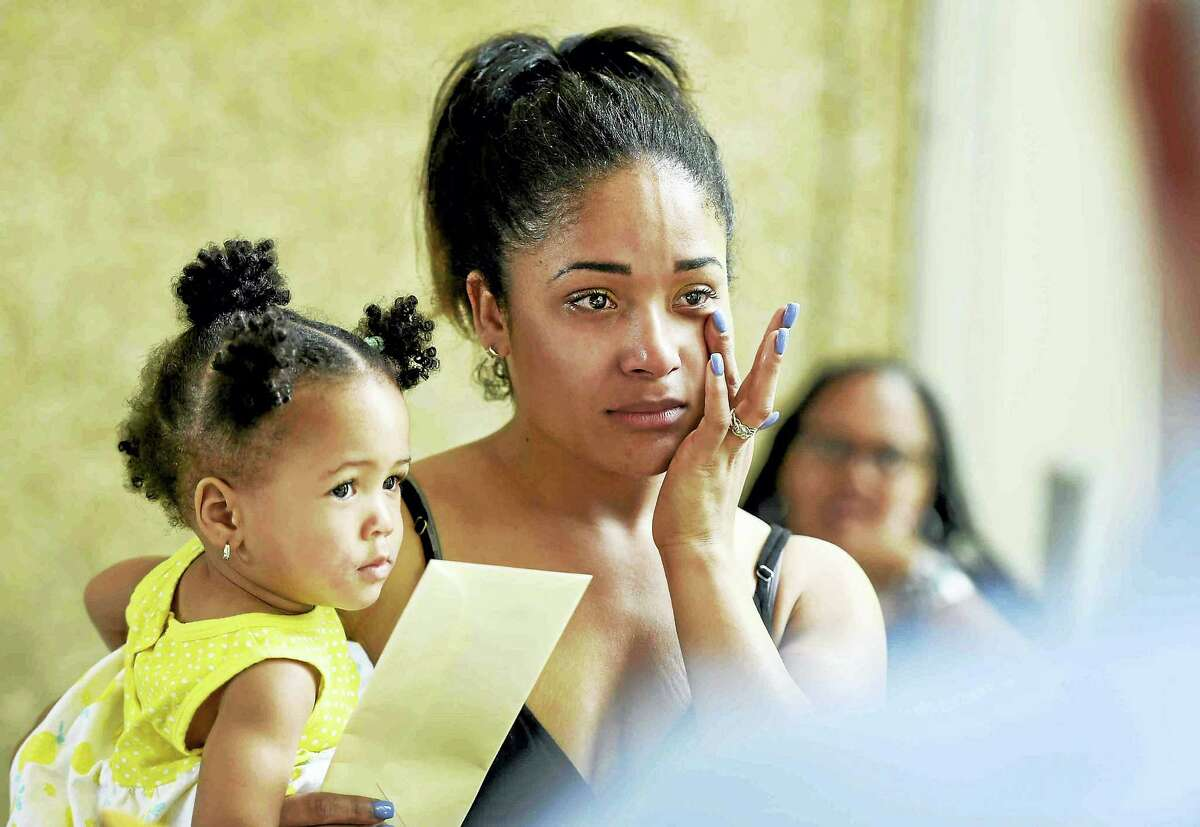 Graduate Jadah L. Moore, with her daughter Aylah Washington, wipes away tears while being awarded the Historic Wooster Square Association Start Bank Scholarship during the New Light High School celebration Tuesday in New Haven.