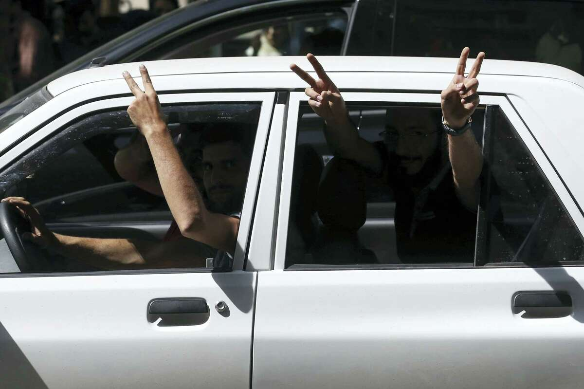 Supporters of Iranian President Hassan Rouhani flash the victory sign from their car outside a polling station for the presidential and municipal councils election, in Tehran, Iran, Friday, May 19, 2017. Millions of Iranians voted late into the night Friday to decide whether incumbent President Hassan Rouhani deserves another four years in office after securing a landmark nuclear deal, or if the sluggish economy demands a new hard-line leader who could return the country to a more confrontational path with the West.