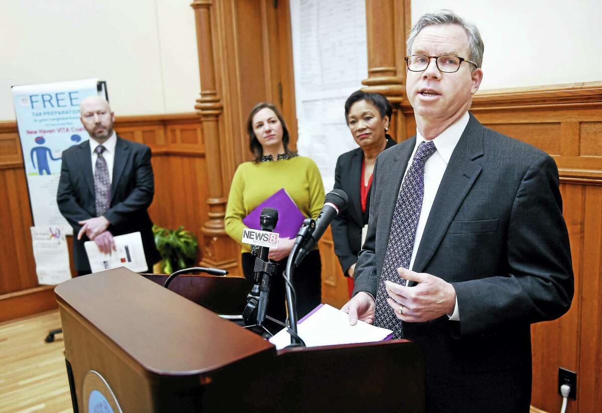 Jim Horan, right, CEO of Connecticut Association for Human Services, speaks at a press conference at New Haven City Hall Tuesday about the VITA program.