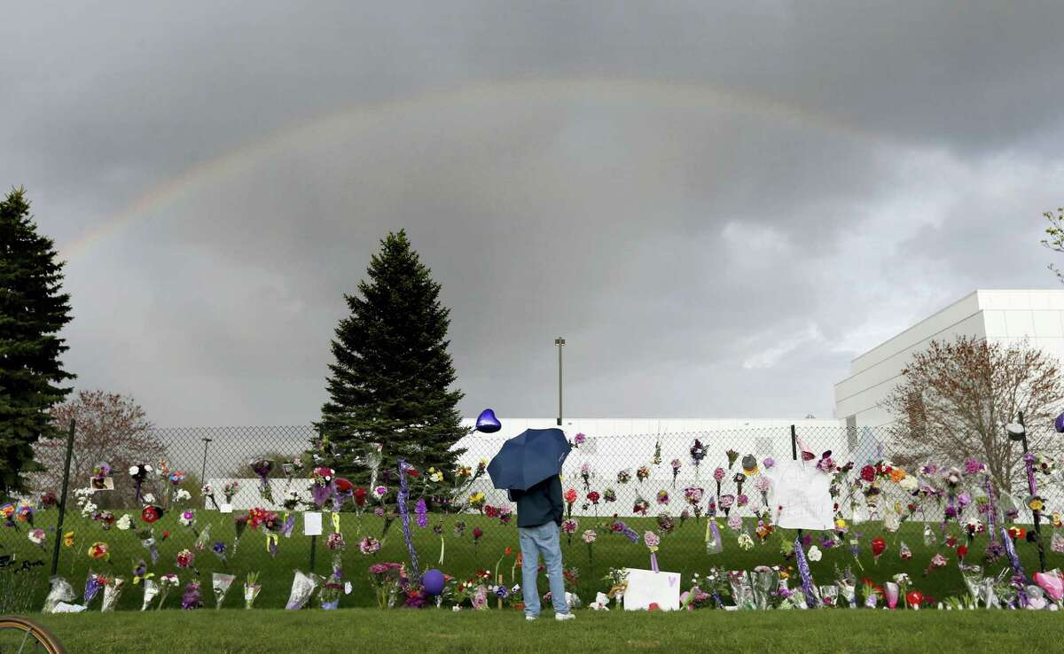 In this April 21, 2016 photo, a rainbow appears over Prince's Paisley Park estate near a memorial for the rock superstar in Chanhassen, Minn. Nearly a year after Prince died from an accidental drug overdose in his suburban Minneapolis studio and estate, investigators still haven't interviewed a key associate nor asked a grand jury to investigate potential criminal charges, according to an official with knowledge of the investigation.