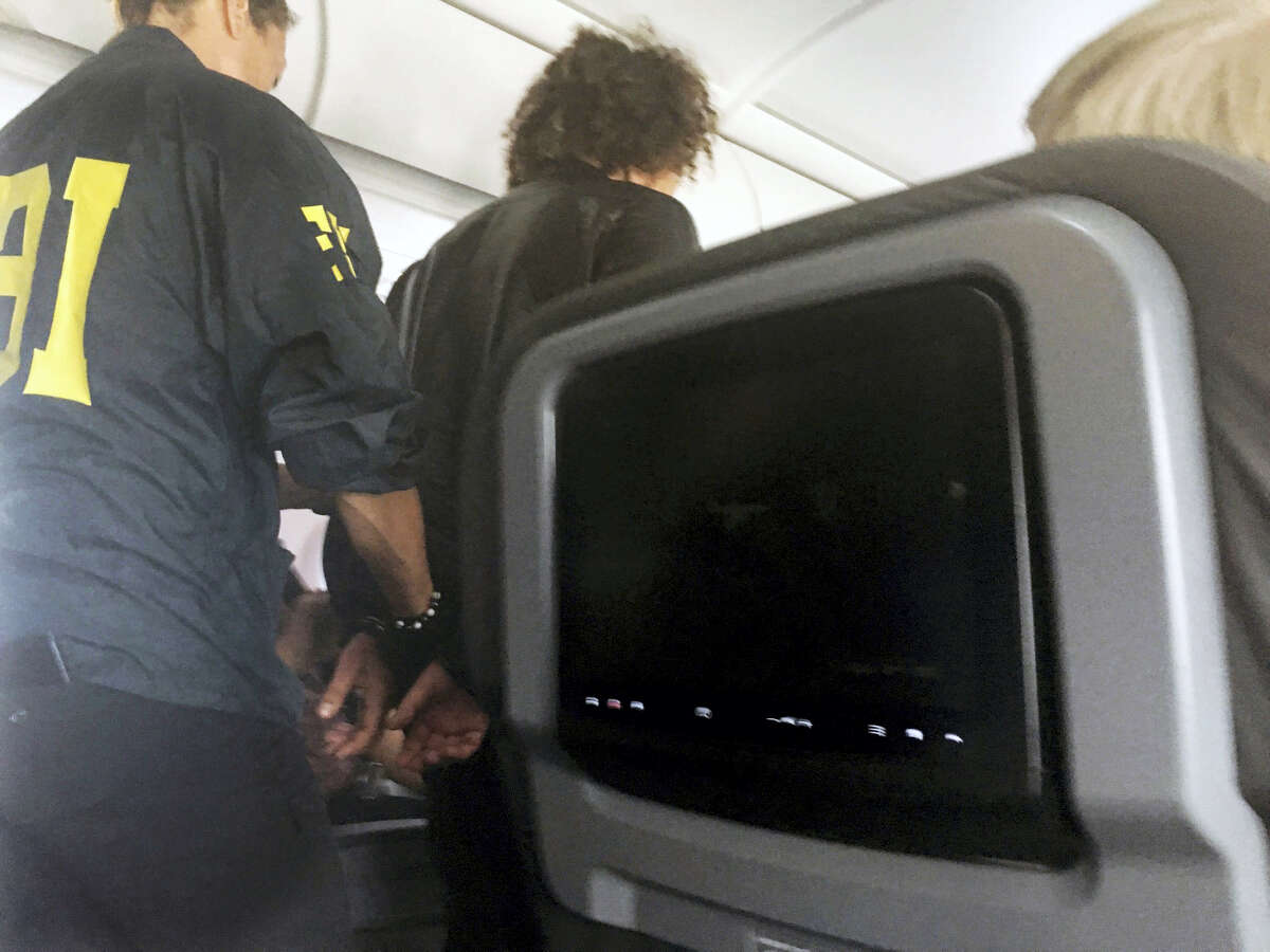 In this photo provided by Donna Basden, a man is escorted off an American Airlines flight after it landed in Honolulu, Friday, May 19, 2017. Federal agents met the plane from Los Angeles when it landed in Honolulu and took the man into custody.